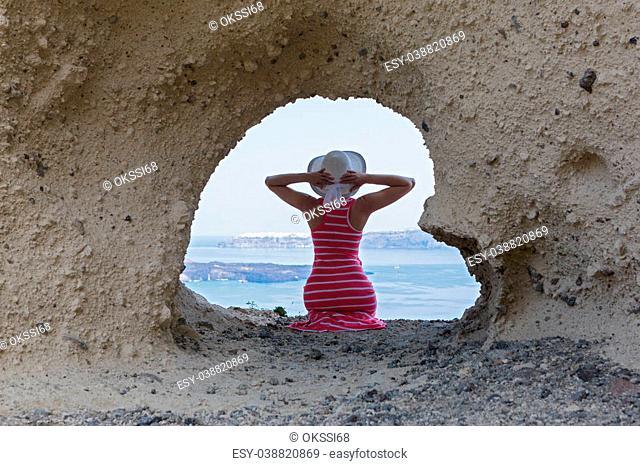 Woman in a long dress sitting on rocks of cliff, near cave in the shape of a heart. Santorini, Greece
