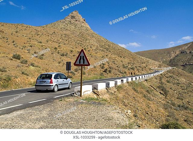 BETANCURIA AREA FUERTEVENTURA Tourist hired car travelling along mountaineous hillside roads
