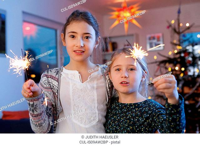 Girls in front of christmas tree holding sparkler looking at camera smiling