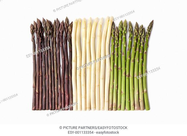 Purple, white and green asparagus on white background