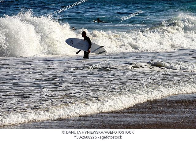 Europe, Portugal, Southern Portugal , Algarve region , Faro district , Sagres, Mareta beach - Praia da Mareta , male surfer entering waters of Atlantic Ocean