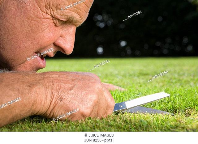 Close up of senior man cutting grass with scissors