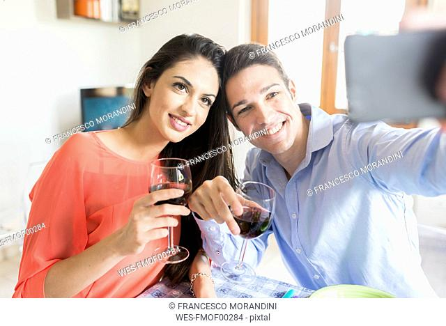 Couple holding red wine glasses posing for a selfie
