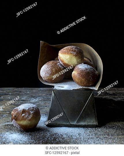 Fresh beignets near set of baked loaf in craft paper with powdered sugar on wooden table