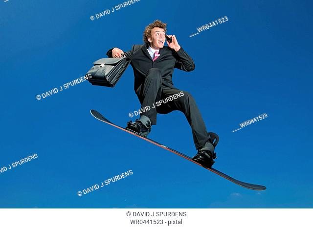 A snowboarding businessman on cell phone