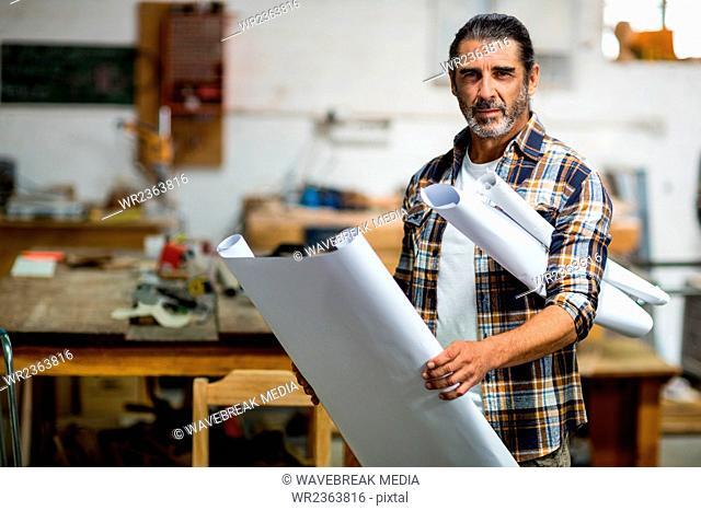 Portrait of carpenter with blueprint