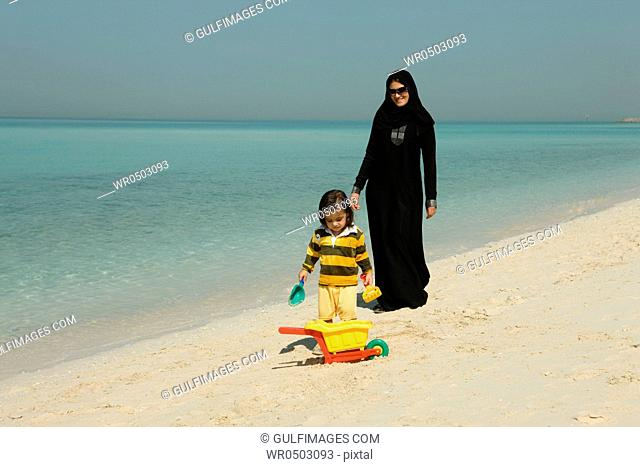 Arab mother and son playing at the beach