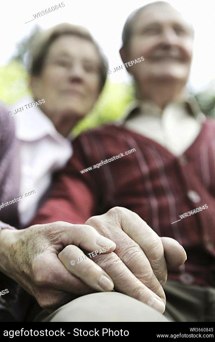 Germany, Cologne, Senior couple holding hands in park
