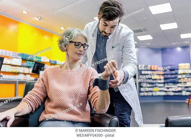 Pharmacist taking blood pressure of customer in pharmacy