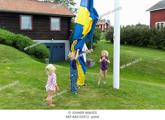 Children lifting Swedish flag