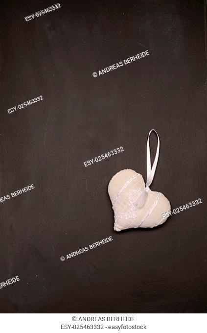 Empty blackboard with a white fabric heart shape, love concept