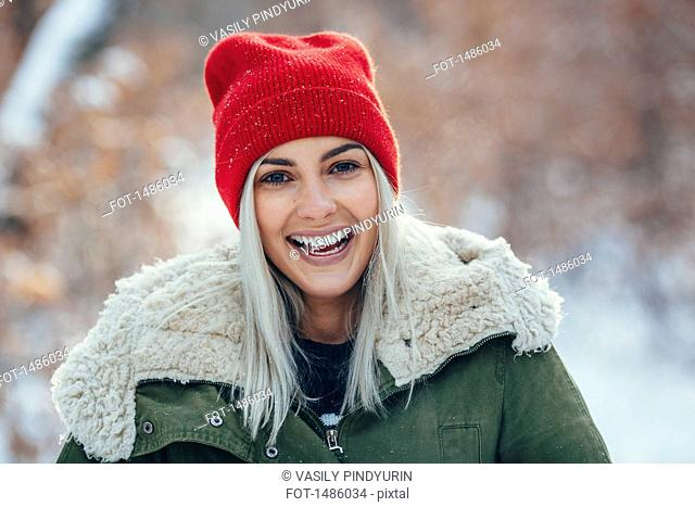 Portrait of happy young woman standing outdoors during winter