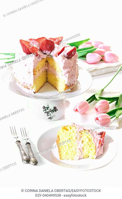Strawberry cake on cake stand with a slice ready to be served on the plate, all on white table decorated with pink tulips