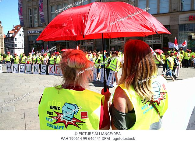 14 June 2019, Thuringia, Erfurt: Retail workers with a red parasol are standing in front of the Anger 1 shopping centre during a strike