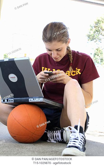 woman texting with a laptop on top of a basketball