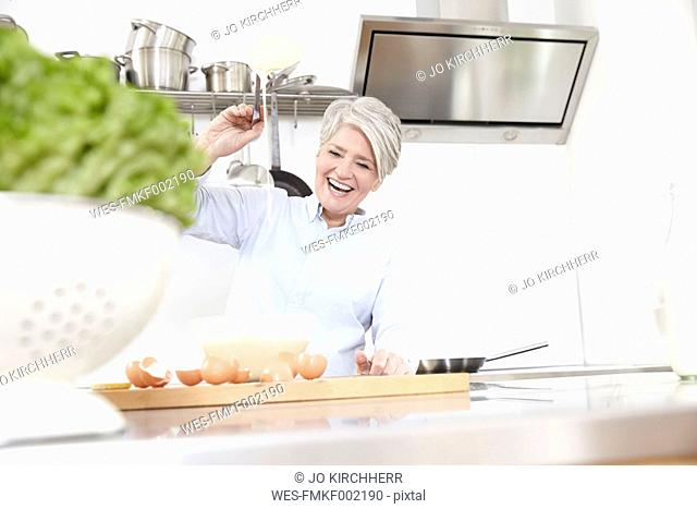Happy mature woman baking in kitchen