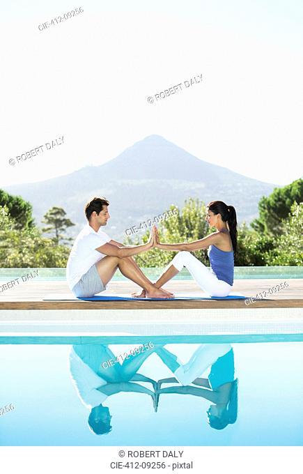 Couple practicing yoga poolside