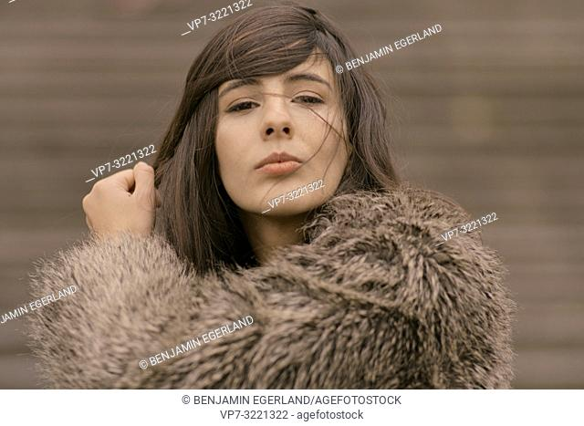 portrait of playful woman curling lips and playing with styled hairs, flirty emotion, in Munich, Germany