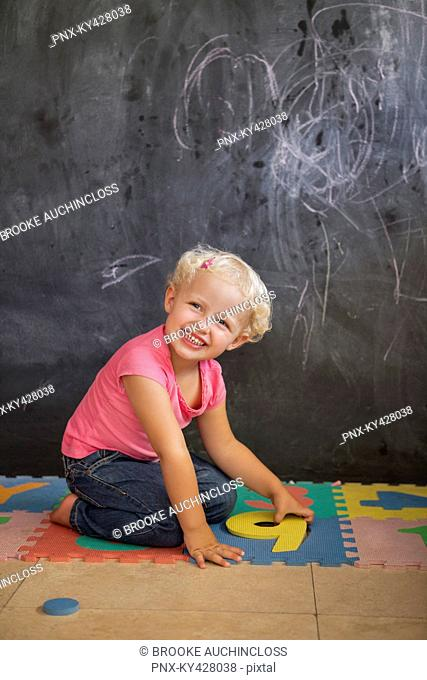 Smiling girl playing with number puzzle in front of a blackboard