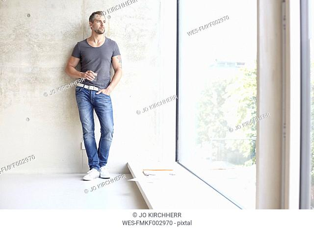 Man holding glass of water looking out of window