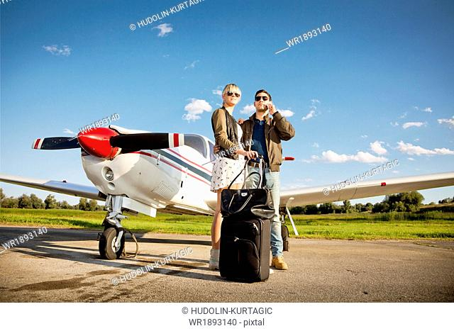 Young couple standing by propeller airplane, man using phone