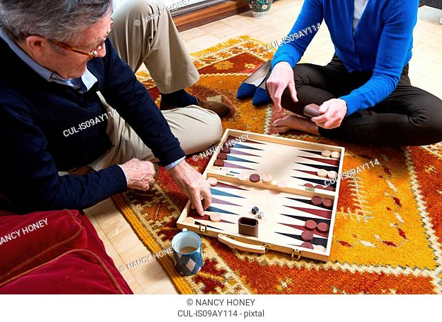 Couple playing backgammon on floor