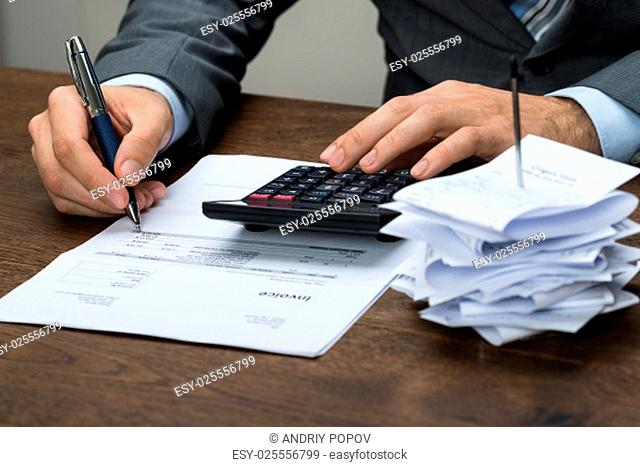 Close-up Of Businessperson Calculating Financial Expenses In Office