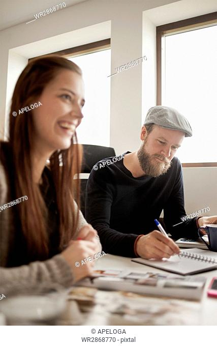 Happy business people working at desk in creative office