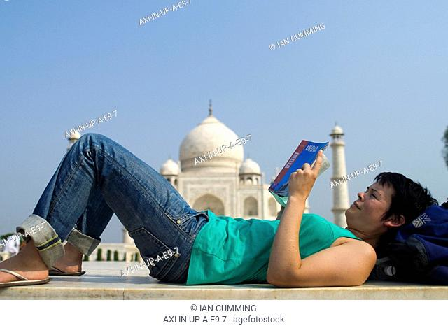 Woman reading guide book in front of the Taj Mahal, Side View