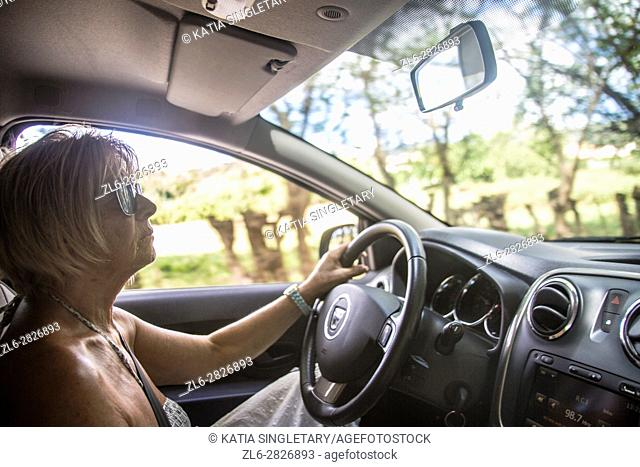 Mature, senior, caucasian woman driving her car on vacation
