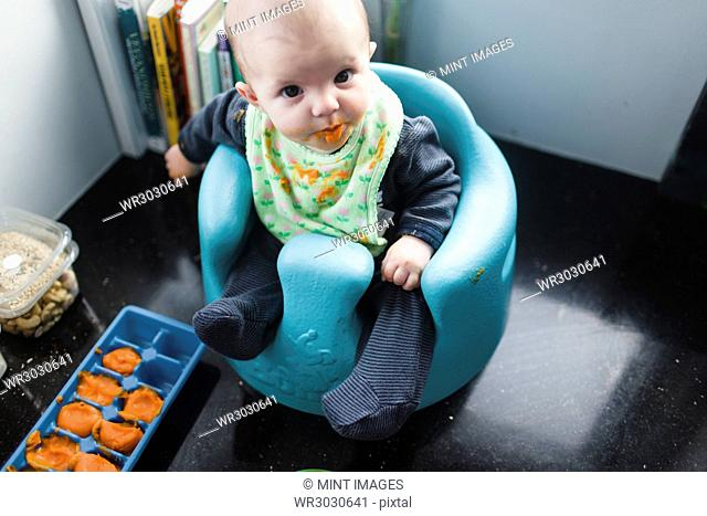 A baby sitting in a chair at a mealtime with food on its face