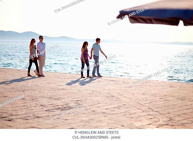Couples walking hand-in-hand on pier