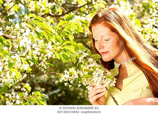 Young woman enjoying spring under blossom tree