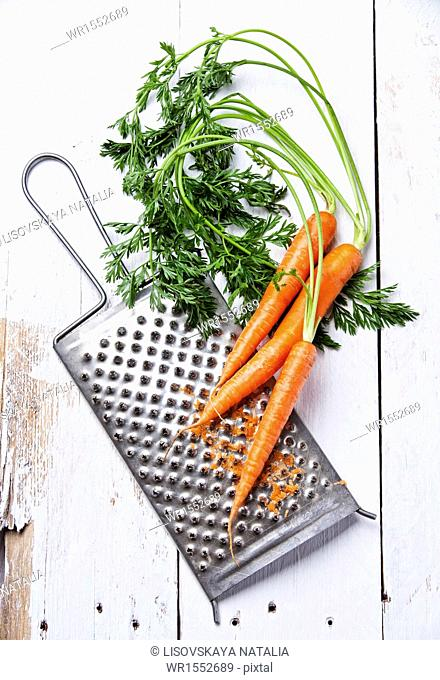 Fresh carrots with grater on white wooden background
