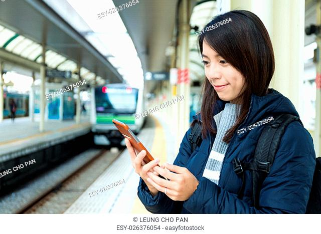 Woman use of mobile phone in trains station