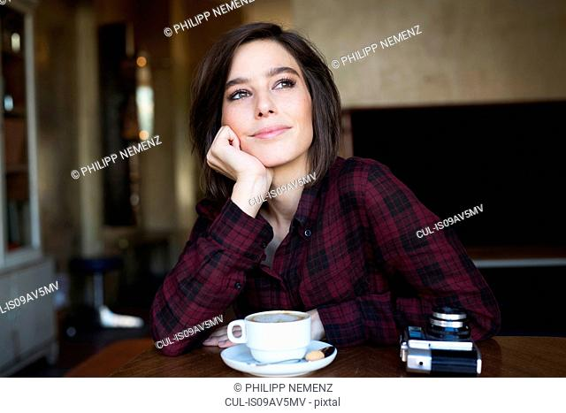 Mid adult woman daydreaming at cafe table