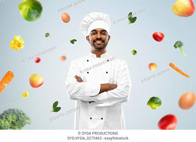 happy male indian chef in toque over vegetables
