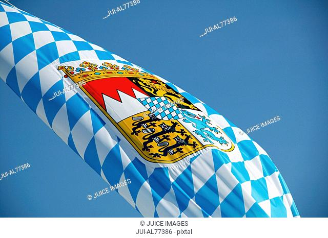 Low angle view of a flag with Bavarian crest against blue sky, Bavaria, Germany