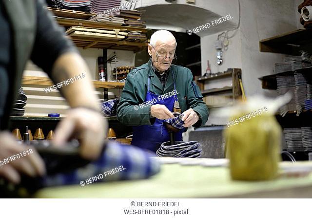 Senior shoemaker working on slippers in workshop