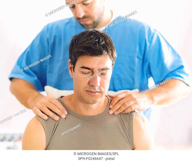 Physiotherapist massaging man's shoulders