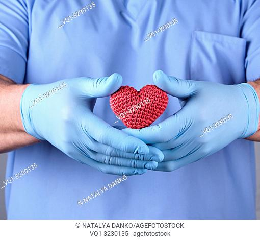 doctor with blue latex gloves holding a red heart, selective focus