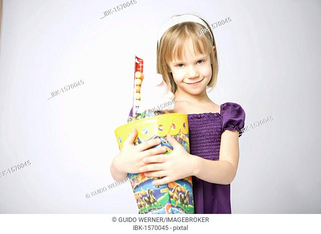 Girl holding a large cornet of cardboard filled with sweets and little presents given to children in Germany on their first day at school