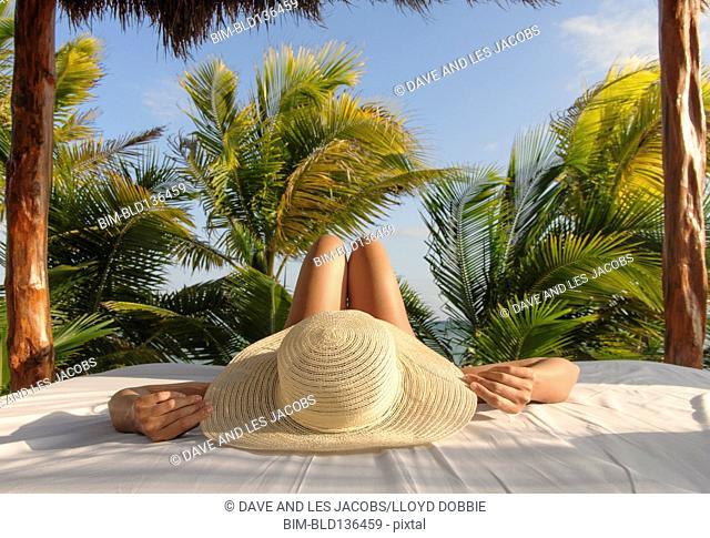 Hispanic woman relaxing in hut on beach