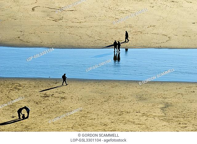 Wales, The Vale of Glamorgan, Southerndown. Silhouettes of people walking on the sandy beach at Dunraven Bay