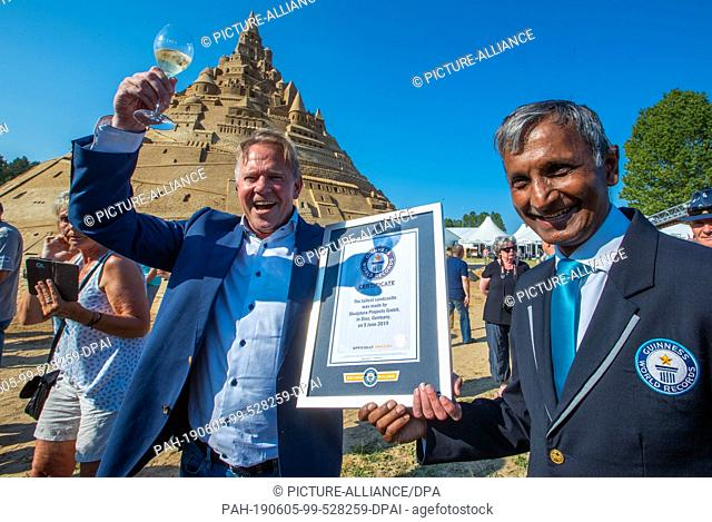 05 June 2019, Mecklenburg-Western Pomerania, Binz: Organizer Thomas van den Dungen (l) celebrates the new world record for the highest sand castle at the sand...