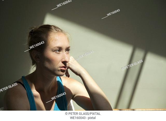 Young serious woman in sunlight, looking to the side