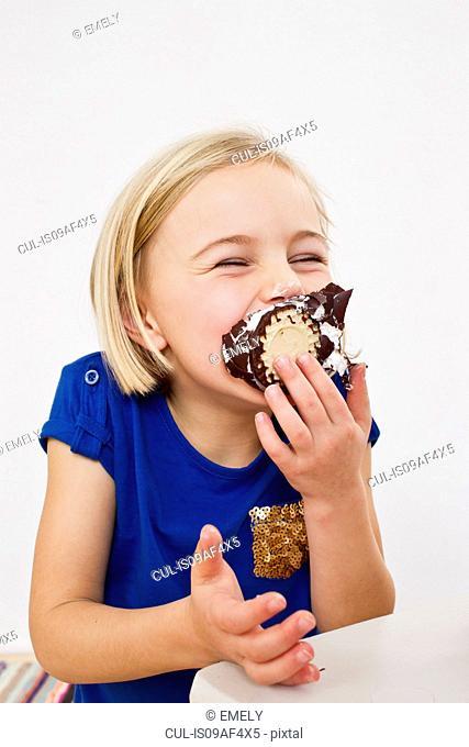 Studio portrait of young girl eating chocolate marshmallow