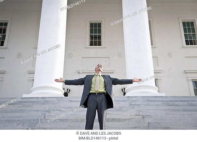 Caucasian businessman standing on steps with arms outstretched