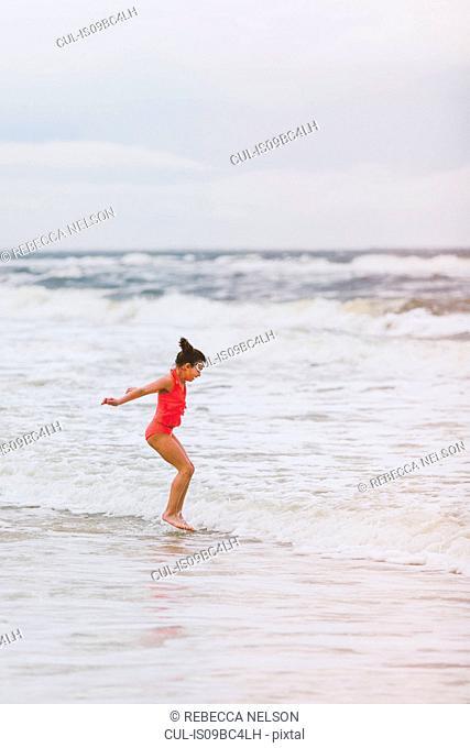 Girl jumping ocean waves, Dauphin Island, Alabama, USA