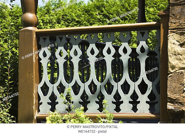 Balusters and railings on the veranda of an old Canadiana residential log home, Quebec, Canada